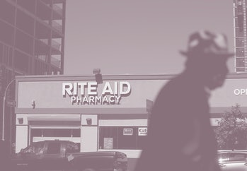 A pedestrian can be seen walking in front of a Rite Aid store.