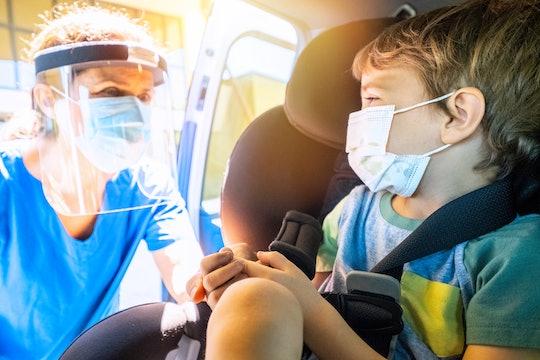 little boy getting a drive through covid test