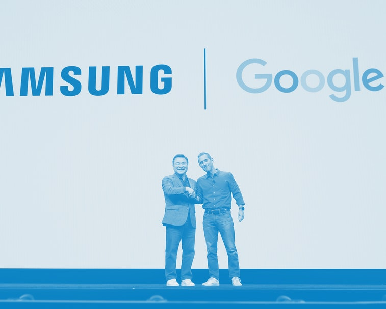Two men shake hands on stage in front of the Samsung and Google logos.