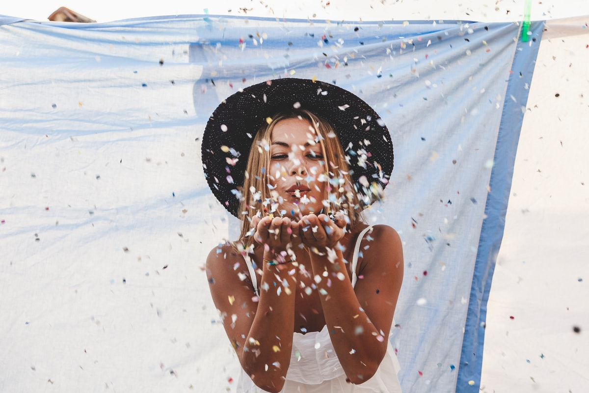 A young woman stands in front of a blue sheet on the beach and blows confetti at a camera.