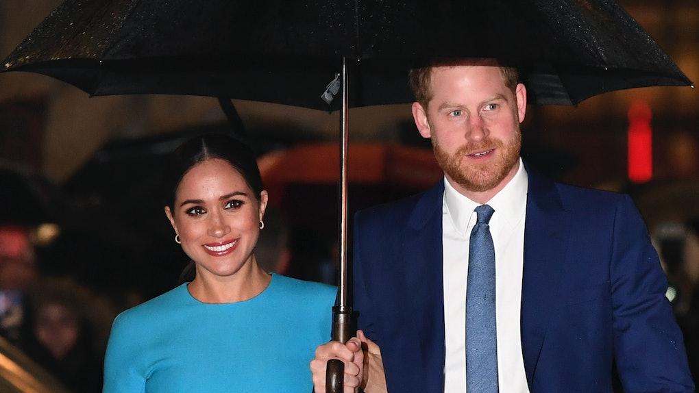 Prince Harry and Meghan Markle share an umbrella.