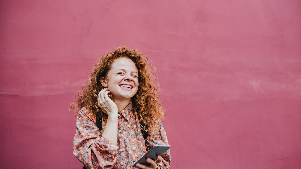 A young woman with red hair stands in front of a hot pink wall with her phone and laughs.