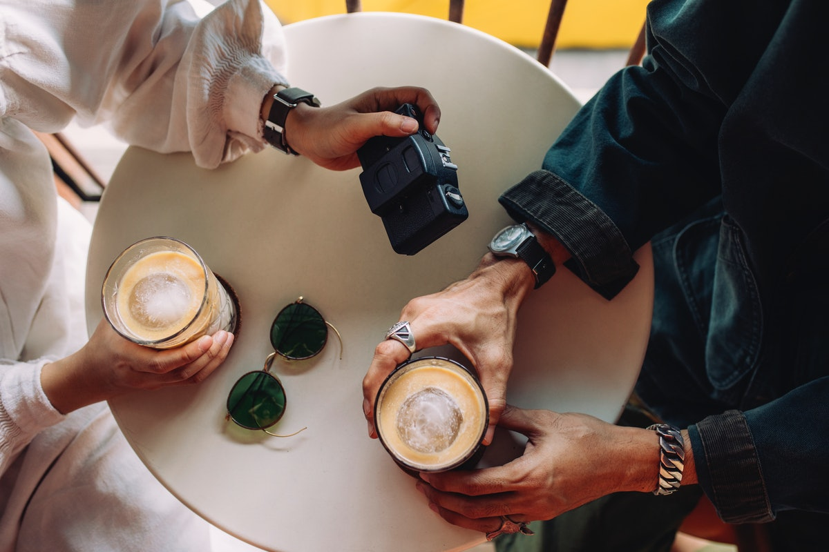 A young couple holds cups of iced coffee and a camera while sitting at a table.