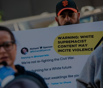 Protestors hold up sign about violent Twitter content.