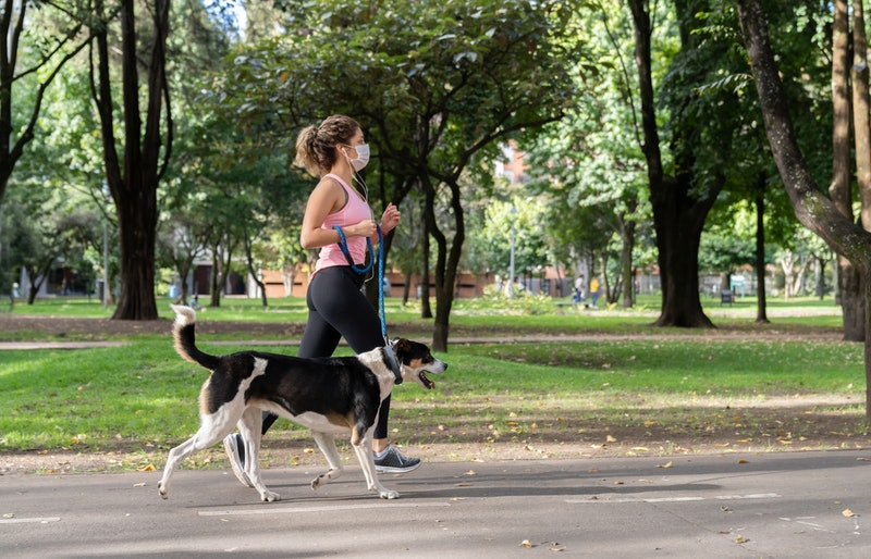 A woman wears a mask while jogging with a dog. Wearing a mask can change the way your body reacts to exercise.