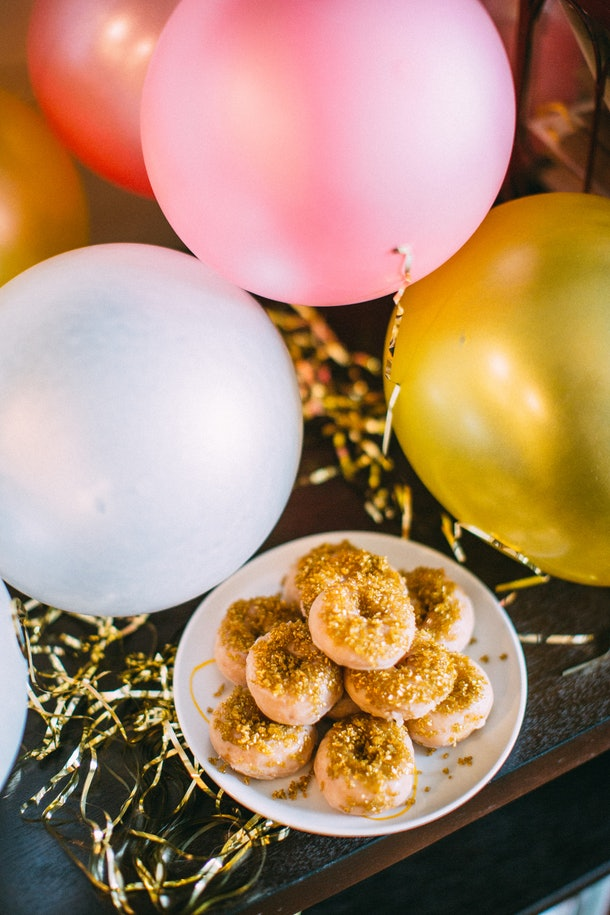 A plate of mini doughnuts sits on a table next to pink and yellow birthday balloons.
