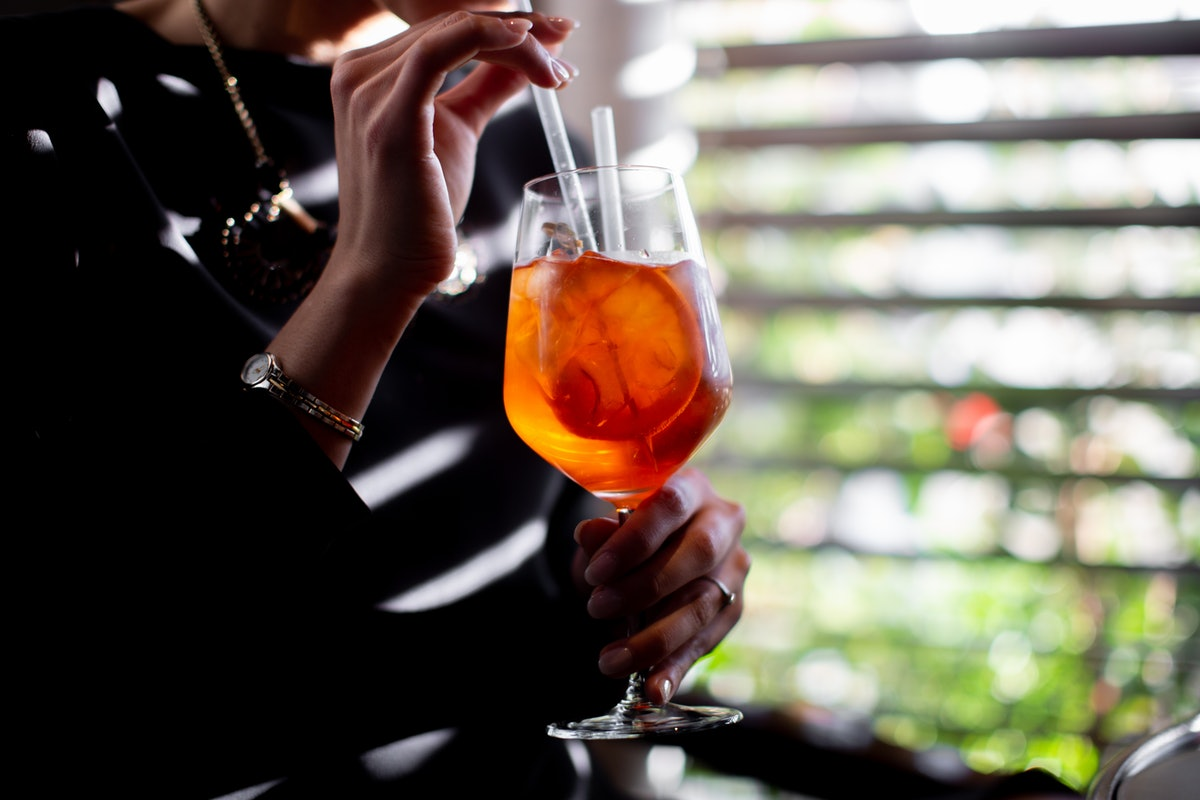 A young woman sips on an Aperol Spritz while sitting near her backyard.