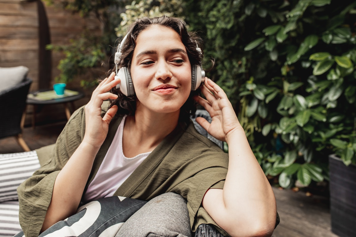 A young woman relaxes in her backyard while wearing a pair of white headphones.