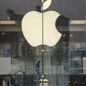 The Apple logo can be seen in the window of an Apple Store.