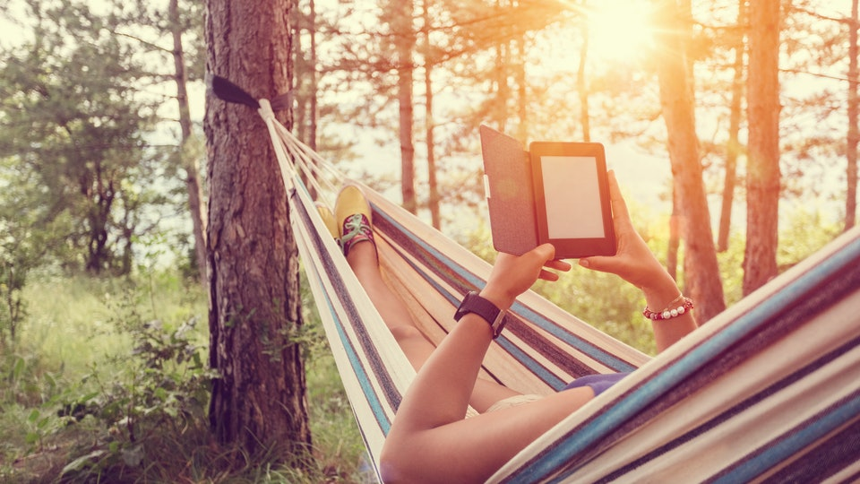 woman in hammock with e-reader