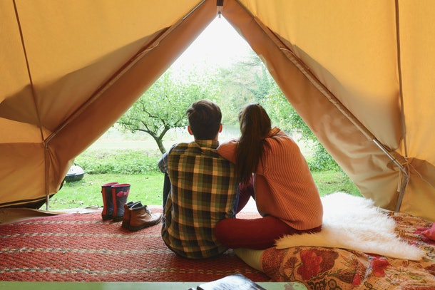 A couple sits in their decorated camping tent.