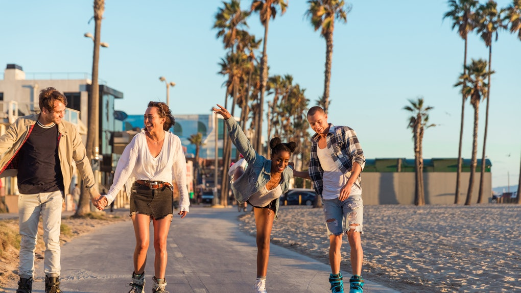 A group of friends wearing roller skates, skate down the beach during the summer.