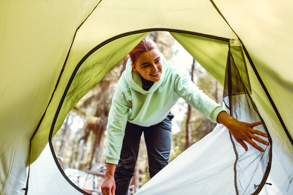 A young woman wearing a green sweatshirt opens up the window of a tent while backyard camping.