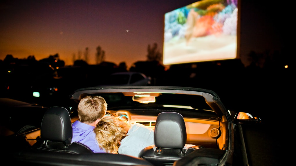 A couple sit in their car at a drive-in movie.