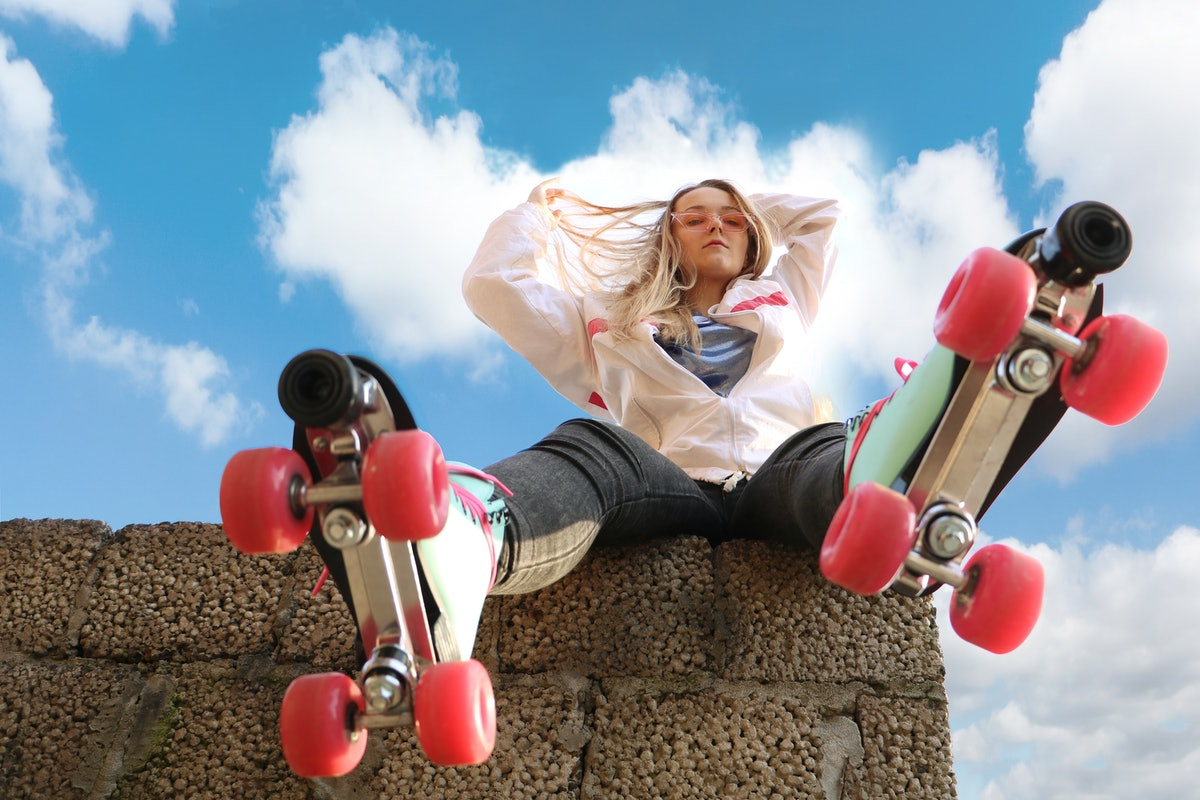 A young woman sits on a concrete ledge and poses with her pink, blue, and white rollerblades.