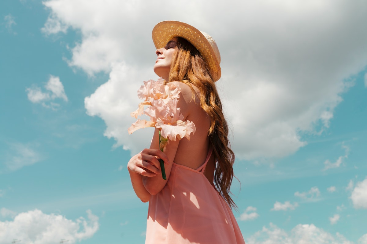 A young woman with long, red hair holds pink flowers and looks up at the sky on a sunny day.