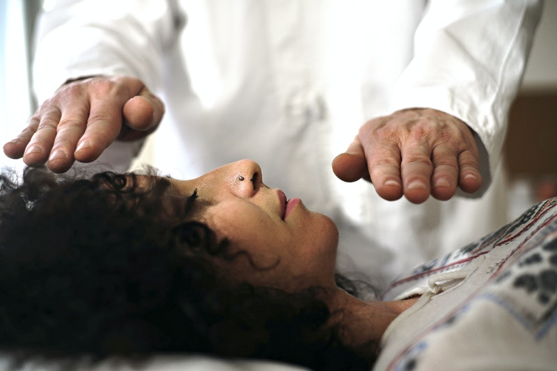 A woman receives reiki healing. Reiki is an alternative therapy originating in Japan.