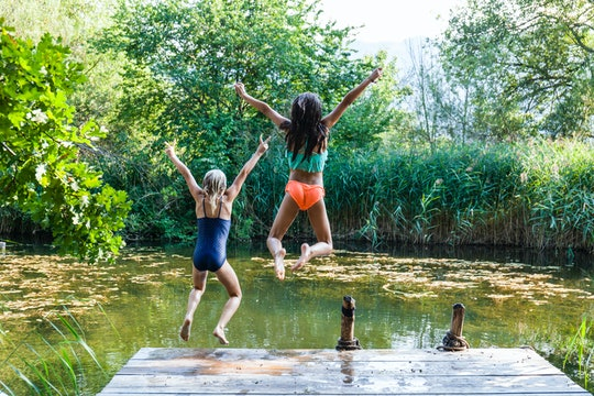 kids jumping into pond
