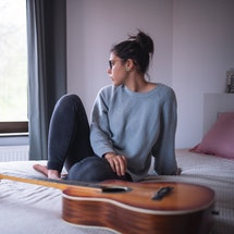 A woman with a guitar stares out a window. If you've had a scary dream, these techniques can help you interpret nightmares and learn from them.