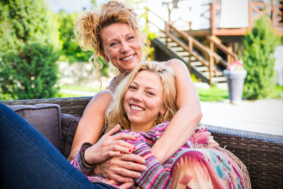 A happy mother and daughter hug, while sitting on a couch in the backyard.
