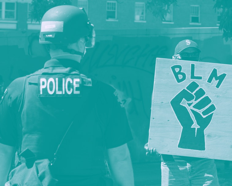 A police officer in uniform faces a protestor with a Black Lives Matter sign.