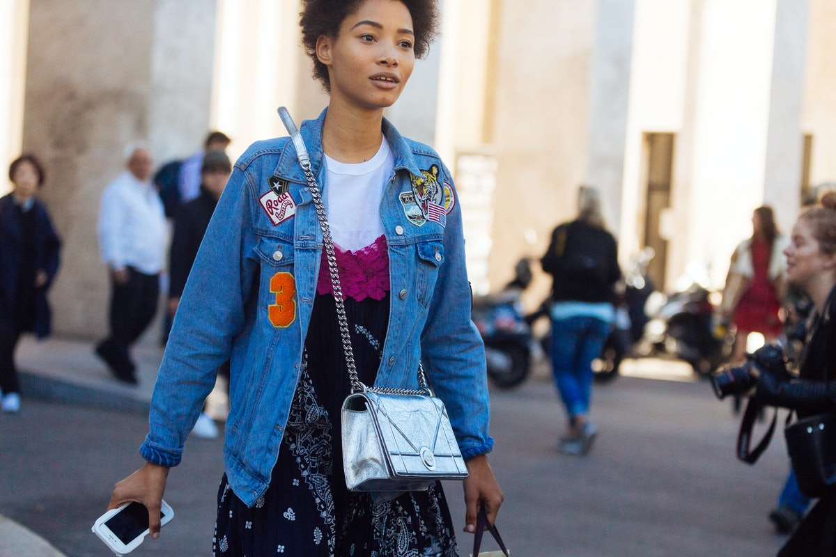 A woman walks through the city with a denim jacket on, covered in patches.