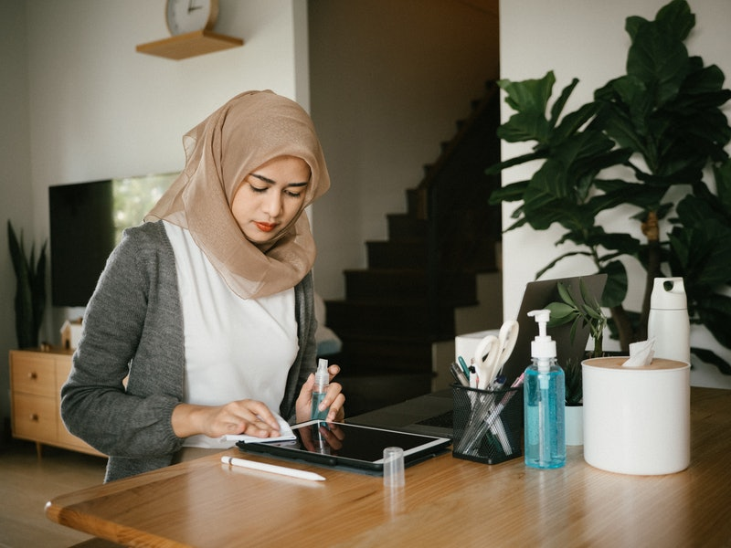A person wearing a hijab cleans and organizes her desk space at home. Employing multiple different types of self-care in your everyday life can help take care of your whole person.