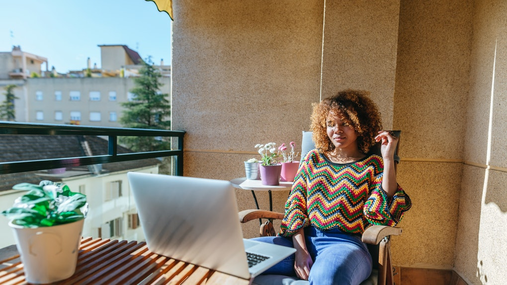 A young Black woman sits at a table on her patio on a sunny day and works remotely.