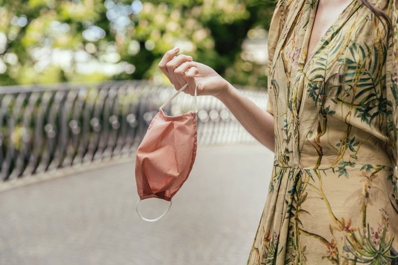 A woman removes her mask on a socially distanced park hang. An expert explains how to manage friendships where one friend isn't taking COVID or social distancing seriously.