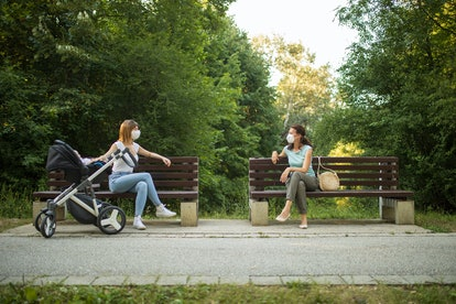 Two friends sit on separate benches at a park. Social distancing has strained even strong friendships, and that's OK.