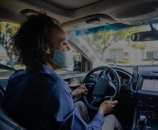 A person drives a car while wearing a mask.