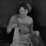 A woman can be seen lifting nylon out of a box while smiling. The photo is black and white.