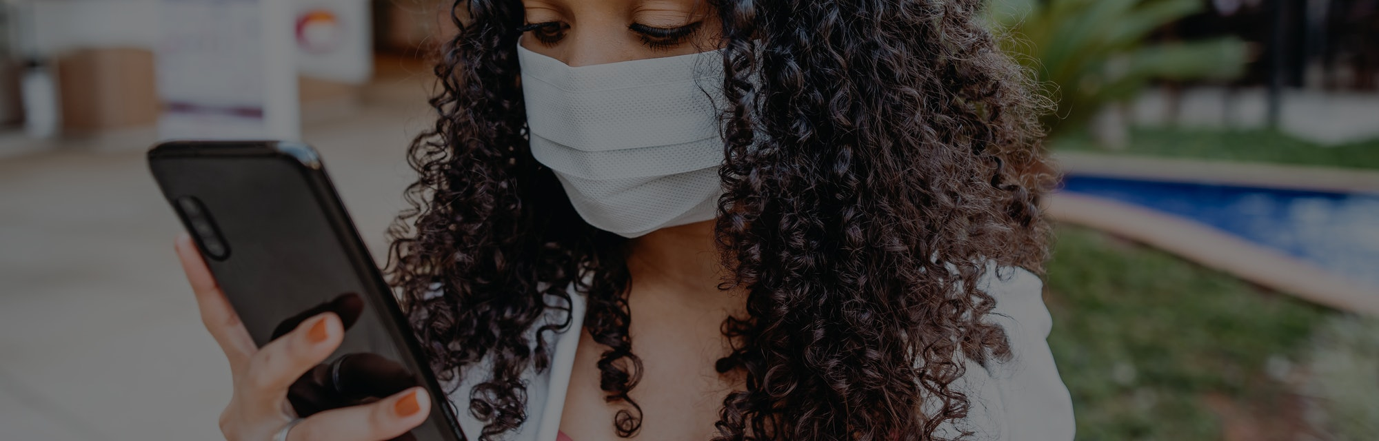 A woman with curly hair can be seen holding a smartphone while she wears a face mask in public.