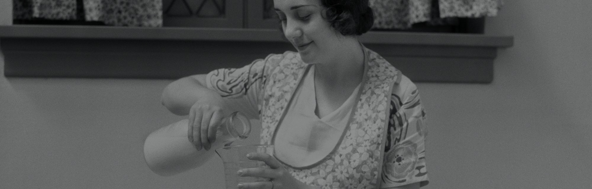 A 1920s image of a young woman preparing food at the table. She can be seen pouring milk from a jug into a measuring glass.