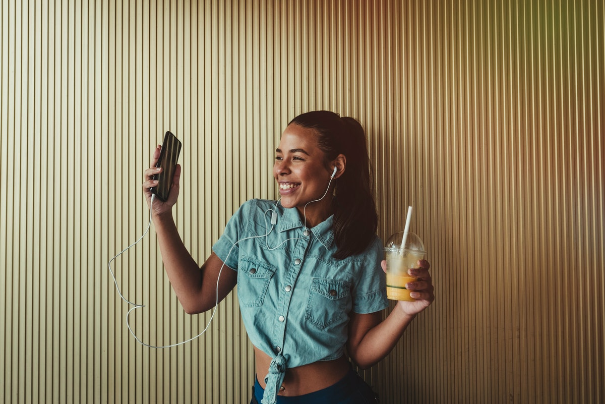 A woman dances with a drink in her hand, while holding her phone.