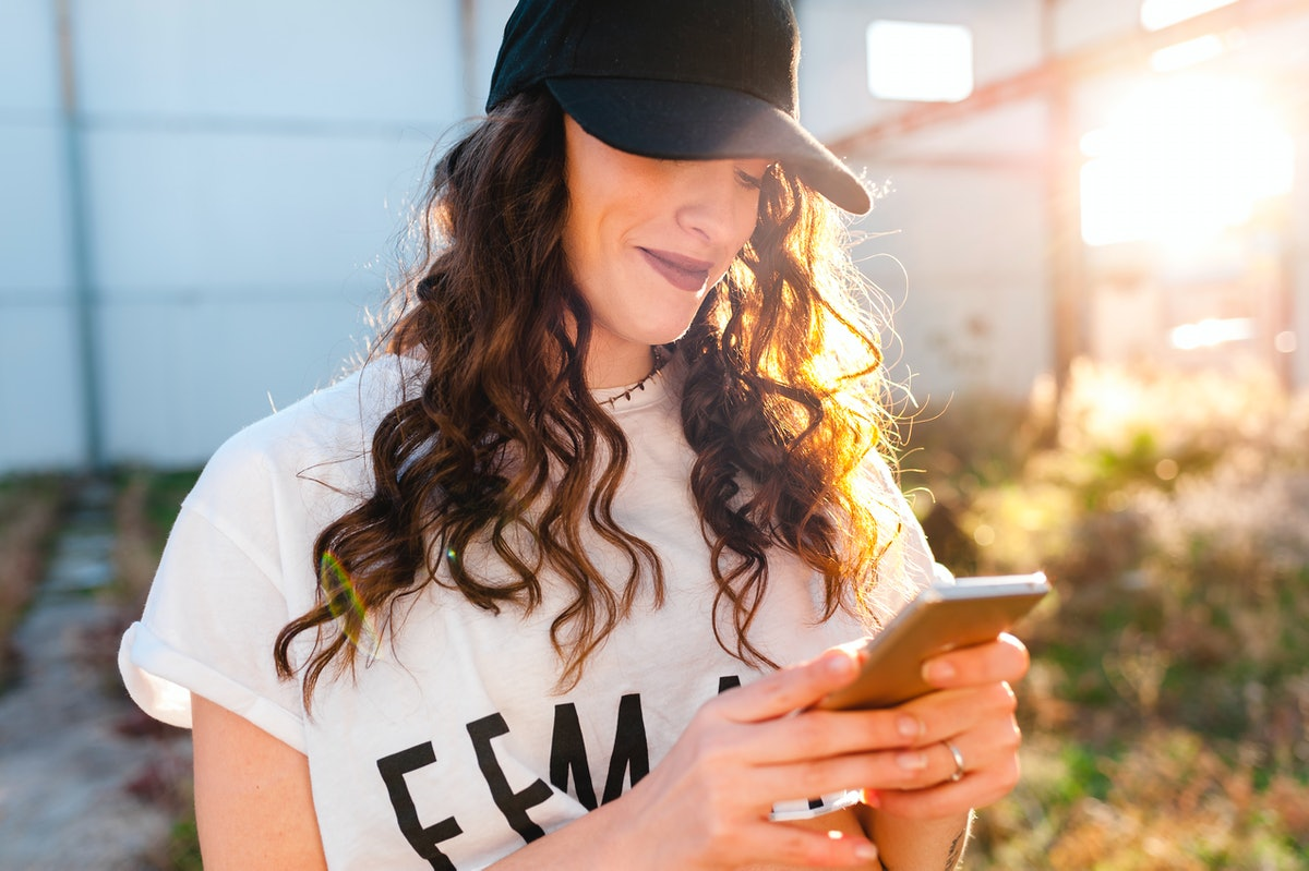 A happy woman wearing a baseball cap types on her phone.