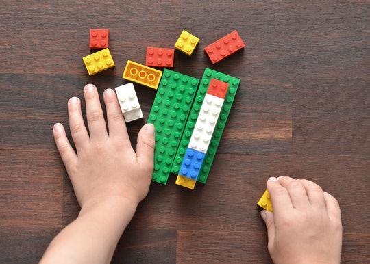 kid hands playing legos