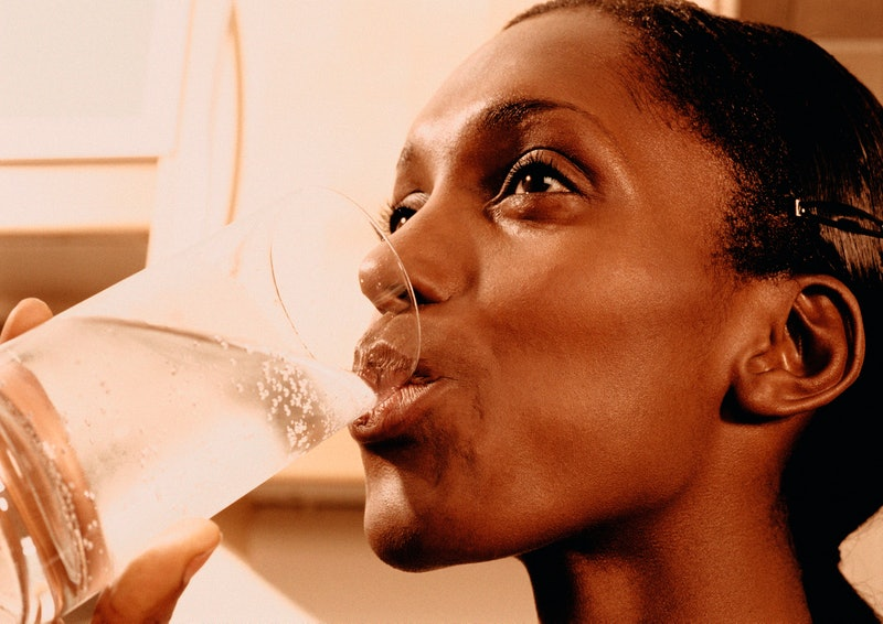 A person smiles as she drinks seltzer. Sparkling water can keep you hydrated just as much as plain water, doctors say.