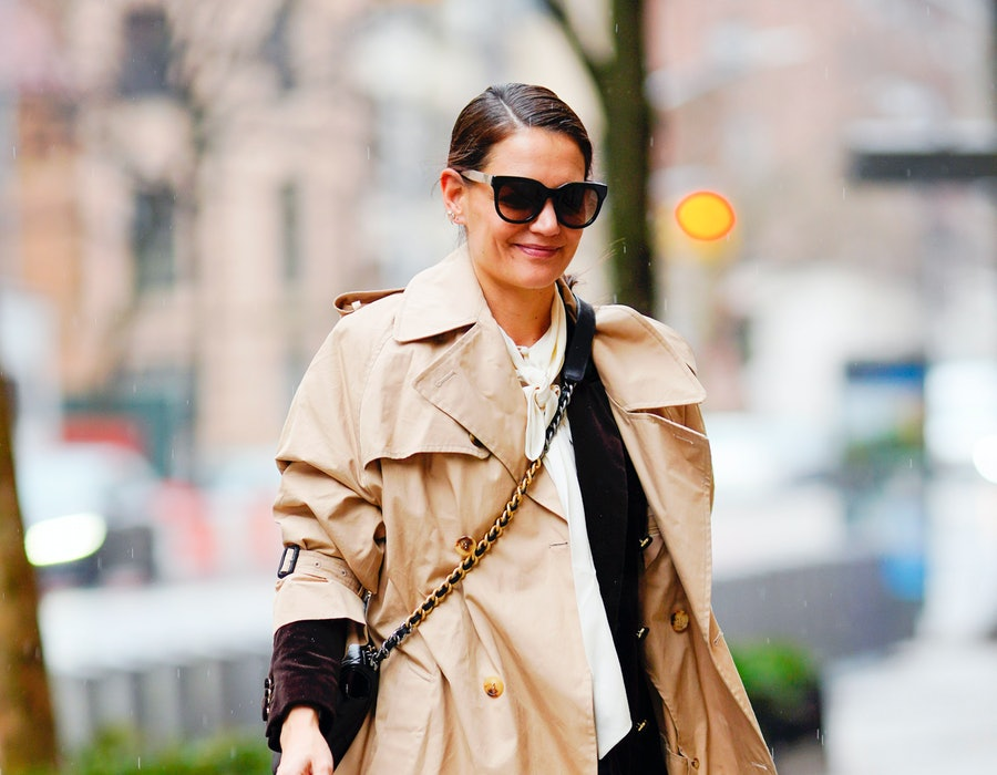 Katie Holmes wearing a beige trench coat while walking in New York City.
