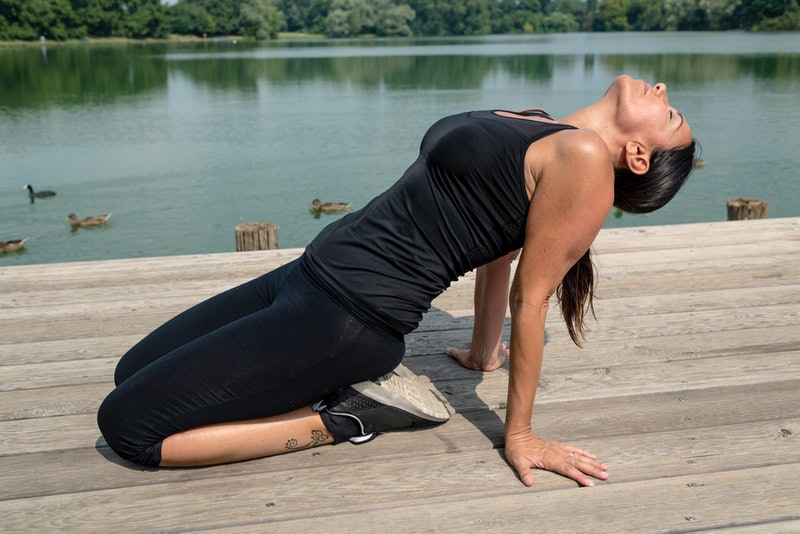 A person performs a backbend outside along a waterfront. Certain yoga flows are especially helpful for easing depression symptoms.