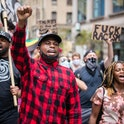 Black Lives Matter activist Derrick Ingram can be seen leading a march. Ingram's right fist is in the air, he has a mask on the lower half of his face, and his shirt is red and black in plaid pattern. There are other protestors carrying anti-racist signs behind Ingram.