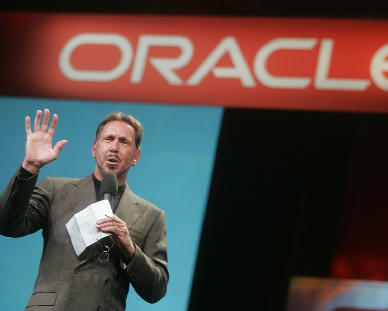 """Larry Ellison stands in front of a sign that reads """"Oracle."""""""