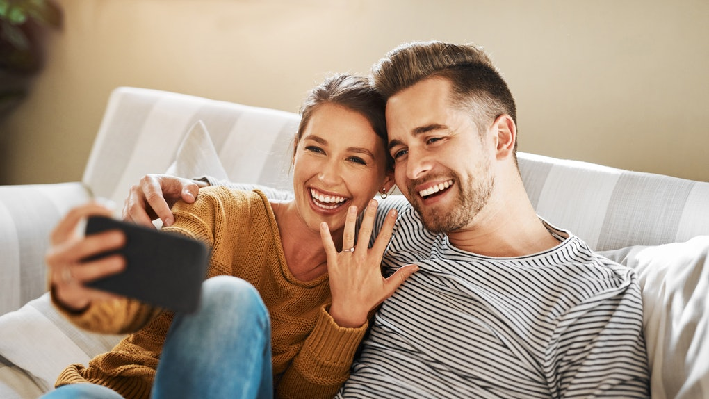 A happy couple takes a selfies, showing off their engagement ring.