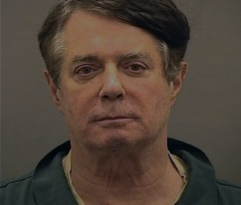 Former Trump presidential campaign chair Paul Manafort can be seen in a mugshot. He is wearing an olive green shirt. He appears exhausted.