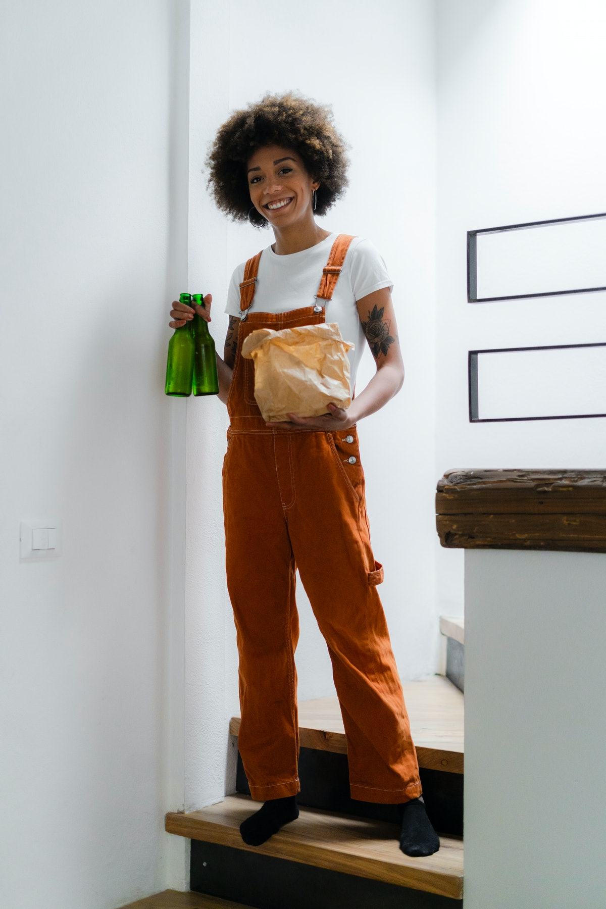 A young and stylish Black woman holds beer bottles and a bag of takeout food while posing on the stairs of her apartment.