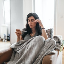 A woman in a blanket takes her temperature at home. Going to the doctor, dentist, and ob-gyn during the coronavirus pandemic for health checkups can be done safely, experts say.