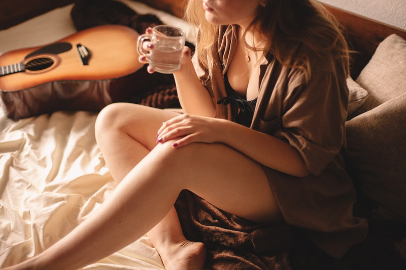 A woman with a guitar in bed drinks water, fending off a hangover. Doctors debunk popular hangover myths.
