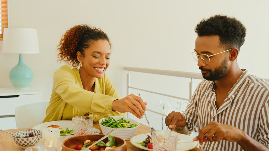 A young Black couple enjoys a fresh meal while sitting at their kitchen table in the summer.