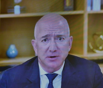 Amazon CEO and owner of The Washington Post, Jeff Bezos, can be seen on a screen, staring into the camera. Bezos is wearing a dark blue tie and blazer with a white shirt. The background depicts a bookcase with several interior decor items on it.
