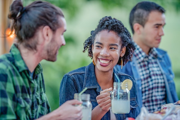 A happy woman smiles at her friend while holding a mason jar filled with lemonade.
